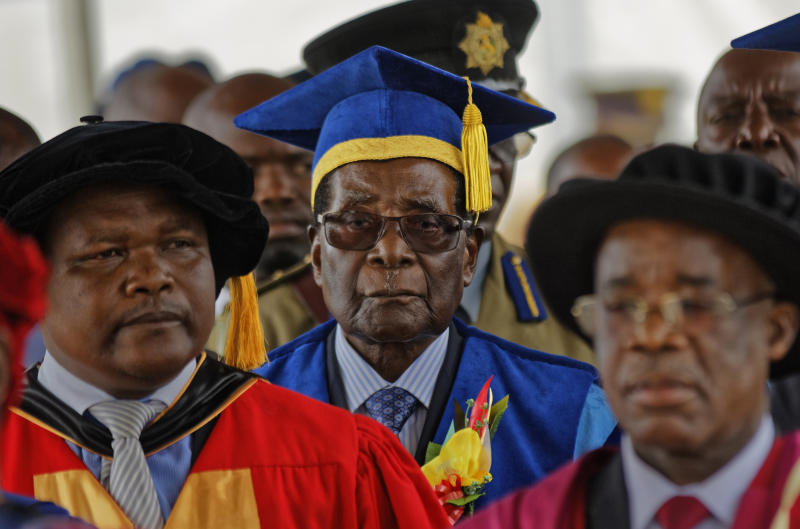 FILE -- In this Friday, Nov. 17, 2017 file photo, Zimbabwe's President Robert Mugabe, center, arrives to preside over a student graduation ceremony at Zimbabwe Open University on the outskirts of the capital, Harare, Zimbabwe. Zimbabwe's presidential spokesman says that former president Robert Mugabe and his wife Grace have traveled to Singapore on their first international trip since he resigned last month. (AP Photo/Ben Curtis, File)