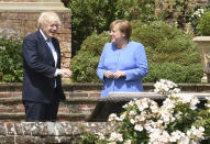 Britain's Prime Minister Boris Johnson, left, and German Chancellor Angela Merkel, walk through the garden at Chequers, the country house of the Prime Minister, in Buckinghamshire, England, Friday July 2, 2021. Johnson is likely to push Angela Merkel to drop her efforts to impose COVID-19 restrictions on British travelers as the German chancellor makes her final visit to Britain before stepping down in the coming months. Johnson will hold talks with Merkel at his country residence on Friday. (Stefan Rousseau/Pool Photo via AP)
