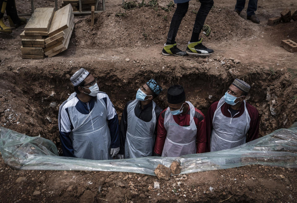"""Members of the Saaberie Chishty Burial Society prepare the grave for the burial of a person who died from COVID-19 at the Avalon Cemetery in Lenasia, Johannesburg Saturday Dec. 26, 2020. South Africa's health minister has announced an """"alarming rate of spread"""" in the country, with more than 14,000 new confirmed coronavirus cases and more than 400 deaths reported Wednesday. It was the largest single-day increase in cases. (AP Photo/Shiraaz Mohamed)"""