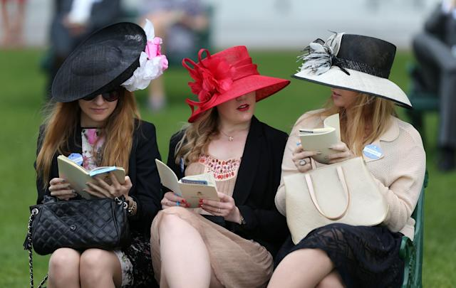 Racegoers study the racecard in the royal enclosure before the start of racing during day four of the Royal Ascot meeting at Ascot Racecourse, Berkshire.
