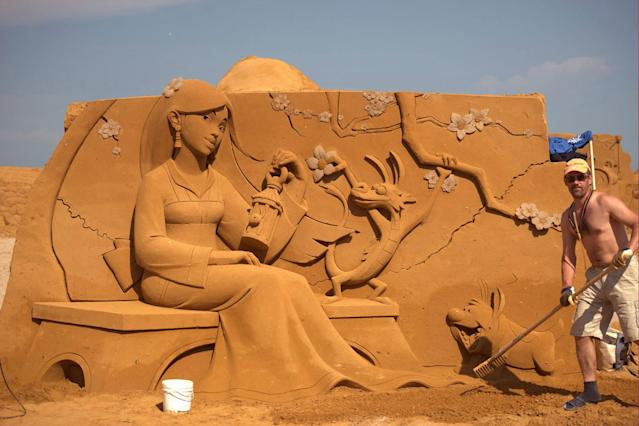 "<p>A sand carver works on a sculpture during the Sand Sculpture Festival ""Disney Sand Magic"" in Ostend, Belgium. (Photo courtesy of Disneyland Paris) </p>"