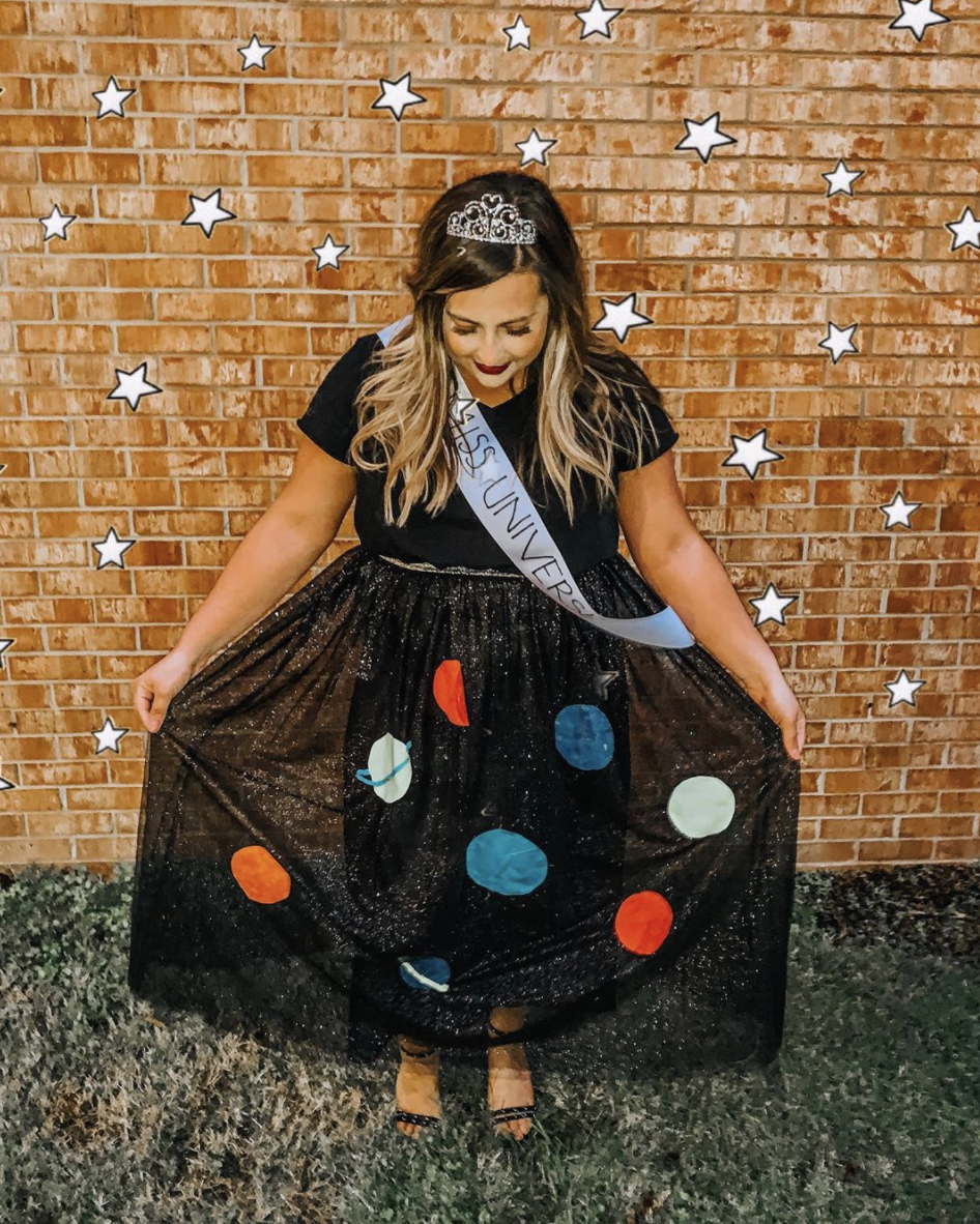 """<p>For a look that's out of this world, glue felt planets to a sparkly skirt, then add a """"Miss Universe"""" sash and a tiara. </p><p><a class=""""link rapid-noclick-resp"""" href=""""https://www.instagram.com/p/B4Td4rDnLof/"""" rel=""""nofollow noopener"""" target=""""_blank"""" data-ylk=""""slk:SEE MORE"""">SEE MORE</a></p><p><a class=""""link rapid-noclick-resp"""" href=""""https://www.amazon.com/Makone-Crystal-Birthday-Wedding-Style-5/dp/B07DGFHY1D?tag=syn-yahoo-20&ascsubtag=%5Bartid%7C10072.g.33547559%5Bsrc%7Cyahoo-us"""" rel=""""nofollow noopener"""" target=""""_blank"""" data-ylk=""""slk:SHOP TIARA"""">SHOP TIARA</a></p>"""