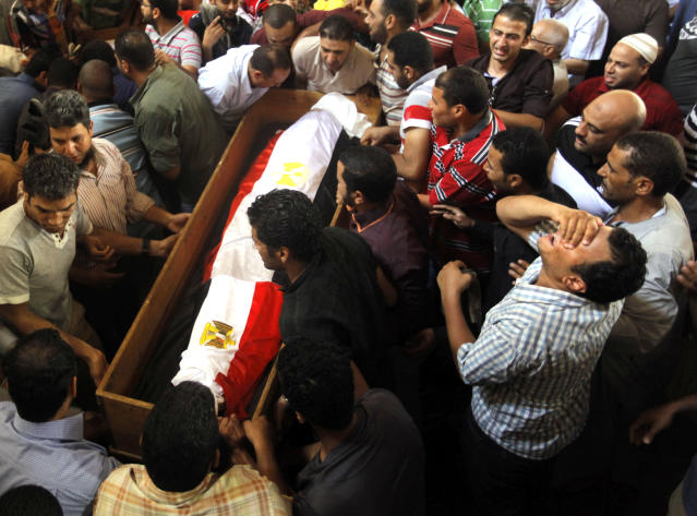 Supporters of Egypt's ousted President Mohammed Morsi carry a coffin, covered with national flag, of their colleague who was killed during Wednesday' clashes, in Amr Ibn Al-As mosque before funeral prayers in Cairo, Egypt, Friday, Aug. 16, 2013. Gunfire rang out over a main Cairo overpass and police fired tear gas as clashes broke out after tens of thousands of Muslim Brotherhood supporters took to the streets Friday across Egypt in defiance of a military-imposed state of emergency following the country's bloodshed earlier this week. (AP Photo/Amr Nabil)