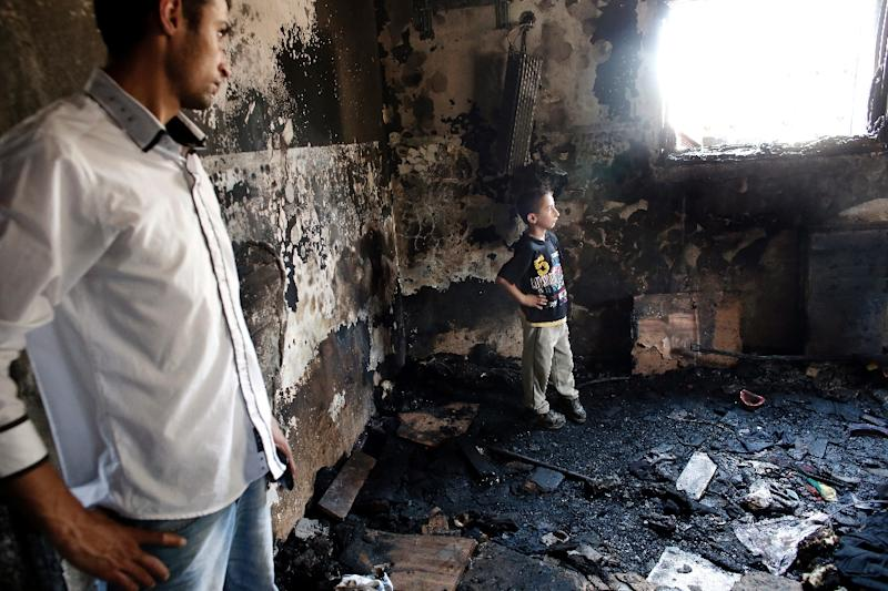 Palestinians survey the damage in a house set on fire by suspected Jewish extremists where 18-month-old Palestinian toddler Ali Saad Dawabsha died