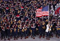 <p>Luger Erin Hamlin of the United States carries the U.S. flag during the Parade of Nations at the opening ceremony, where the team wears uniforms designed by Ralph Lauren. Key items include the fringe suede gloves and intarsia wool sweaters. (Photo: Valery Sharifulin\TASS via Getty Images) </p>