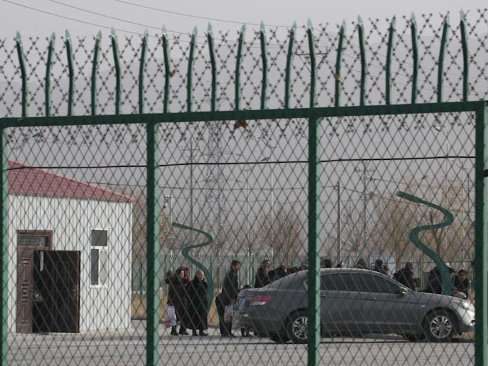 """People line up at a """"re-education"""" centre in Xinjiang province, China, in December 2018: AP Photo/Ng Han Guan, File"""