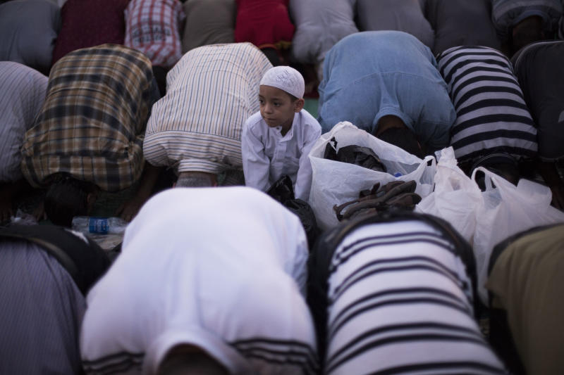 An Egyptian child looks up while praying with supporters of Egypt's ousted President Mohammed Morsi during a protest near Cairo University in Giza, Egypt, Sunday, Aug. 4, 2013. (AP Photo/Manu Brabo)