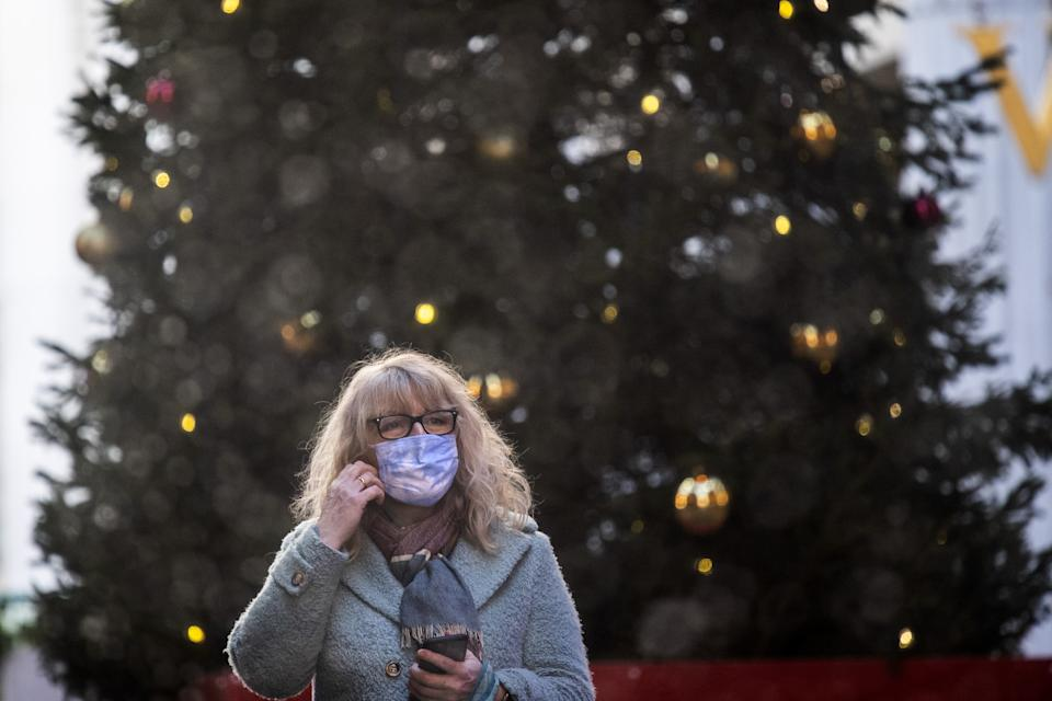 A woman wearing a face mask in front of a Christmas tree in the Leadenhall Market in London . (Photo by Victoria Jones/PA Images via Getty Images)