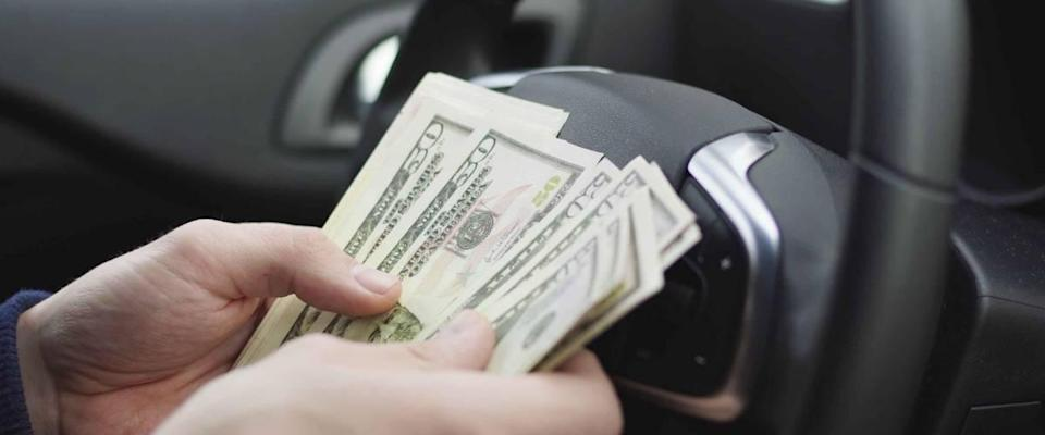 Man counting dollar bills sitting in a car, Close up of male hands count money cash. Concept of earnings or bribes, insurance or credit, investing