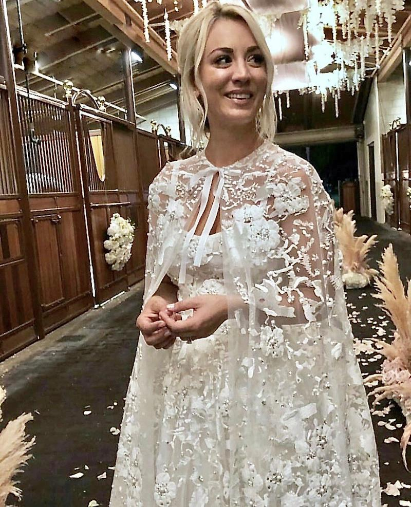 Before she put her hair in a ponytail and switched into her cozier Tadashi Shoji jumpsuit to celebrate, Cuoco wore a lacy Reem Acra gown and cape to marry Cook.