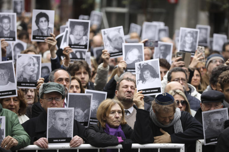 People hold up pictures of people who died during the bombing at the AMIA Jewish center that killed 85 people on the 25th anniversary of the attack in Buenos Aires, Argentina, Thursday, July 18, 2019. (AP Photo/Natacha Pisarenko)