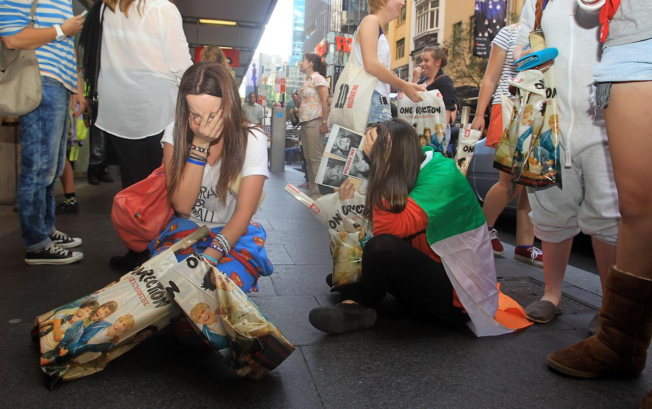 SYDNEY, AUSTRALIA - APRIL 07:  Young female fans are seen crying after purchasing merchandise at the One Direction promotional store opening on Pitt Street on April 7, 2012 in Sydney, Australia. The store is the only official One Direction merchandise retail venue in Australia and will only be open until April 20. One Direction kicks off thier Australian tour in Sydney next week.  (Photo by Mark Metcalfe/Getty Images)