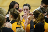 Iowa guard Caitlin Clark, center, huddles with teammates during a timeout in the second half of an NCAA college basketball game against Ohio State, Wednesday, Jan. 13, 2021, in Iowa City, Iowa. Clark, one of the top scorers in the nation, has been named the Big Ten's player of the week three times this season and has won the conference's freshman of the week honor six times. (AP Photo/Charlie Neibergall)