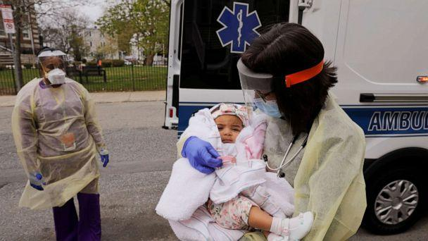 PHOTO: Boston Medical Center pediatrician Dr. Sara Stulac holds five month-old Nairobi Kyra Osorio before Dr. Stulac and nurse Angelee Bullock perform a routine check-up in an ambulance in front of Osorio's home in Boston, Massachusetts, on May 8, 2020. (Brian Snyder/Reuters)