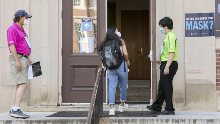 Safety ambassadors Paul Ensslin, left, and Matthew Porter, right, assist a UNC-Chapel Hill student into class on Aug. 10. (Ted Richardson/Washington Post via Getty Images)