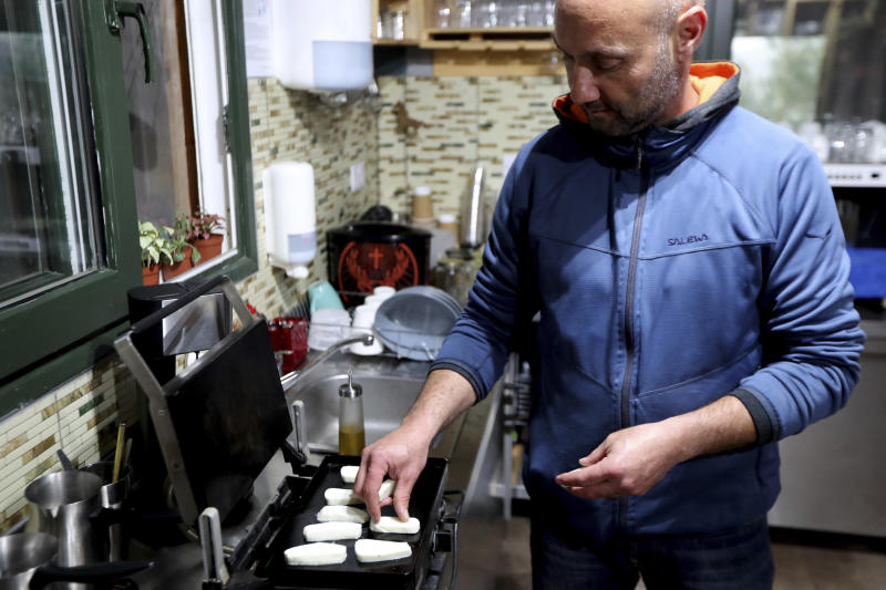 In this photo taken Wednesday Dec. 11, 2019, Cypriot farmer Vasilis Kyprianou, 48, roasts Cyprus' halloumi cheese at his farm in Kampia village near Nicosia, Cyprus. Cyprus' halloumi cheese, with a tradition dating back some five centuries, is the island nation's leading export. It's goat and sheep milk content makes it a hit with health-conscious cheese lovers in Europe and beyond. It's added appeal is that unlike other cheeses, it doesn't melt when heated up. (AP Photo/Petros Karadjias)