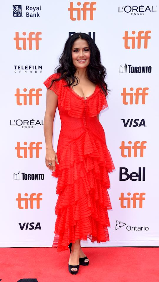 "<p>Hayek wowed audiences in a bright red layered dress by Alexander McQueen at the premiere of her film, ""The Hummingbird Project."" </p>"