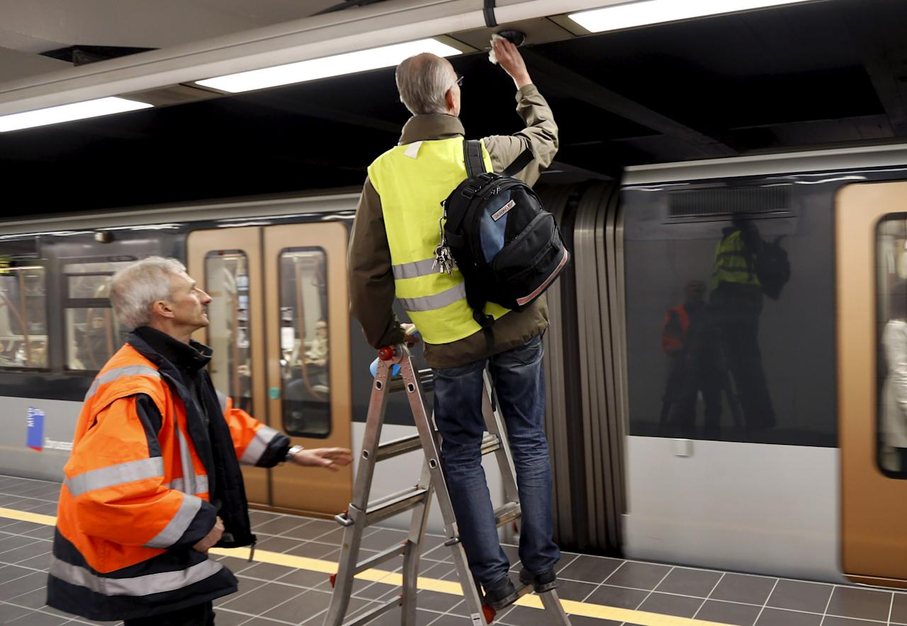 Workers clean a security camera on a platform after Maelbeek metro station reopened on Monday in Brussels, Belgium, April 25, 2016. REUTERS/Francois Lenoir
