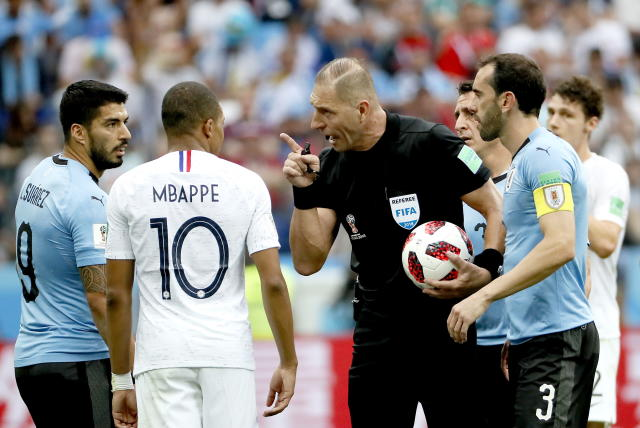 Nizhny Novgorod (Russian Federation), 06/07/2018.- Referee Nestor Pitana of Argentina (C) argues with Luis Suarez of Uruguay (L) and Kylian Mbappe of France (2L) during the FIFA World Cup 2018 quarter final soccer match between Uruguay and France in Nizhny Novgorod, Russia, 06 July 2018. (RESTRICTIONS APPLY: Editorial Use Only, not used in association with any commercial entity - Images must not be used in any form of alert service or push service of any kind including via mobile alert services, downloads to mobile devices or MMS messaging - Images must appear as still images and must not emulate match action video footage - No alteration is made to, and no text or image is superimposed over, any published image which: (a) intentionally obscures or removes a sponsor identification image; or (b) adds or overlays the commercial identification of any third party which is not officially associated with the FIFA World Cup) (Mundial de Fútbol, Rusia, Francia) EFE/EPA/ETIENNE LAURENT EDITORIAL USE ONLY