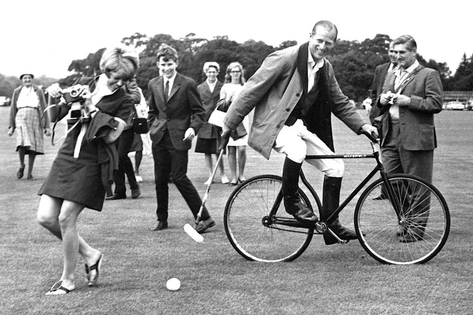 <p>Prince Philip laughs while practising his bicycle polo technique in Windsor Great Park, Berkshire in 1964.</p>