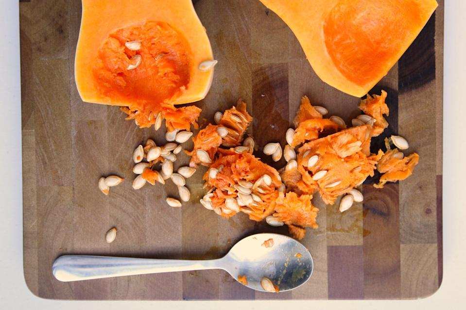 <p>Use a spoon to scoop out the stringy pulp and the seeds. Set aside.</p>