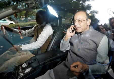 FILE PHOTO: Indian Finance Minister Arun Jaitley speaks on the phone as he leaves a meeting at the prime minister's residence in New Delhi