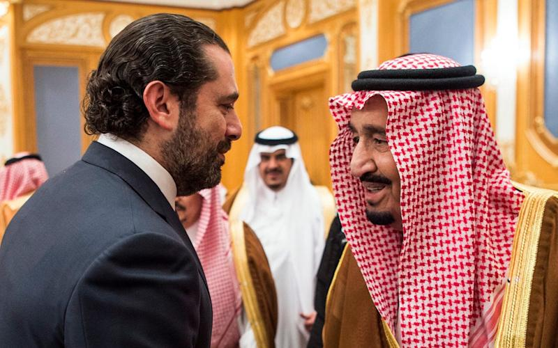 A handout picture provided by the Saudi Royal Palace on November 11, 2017, shows King Salman bin Abdulaziz al-Saud (R) shaking hands with former Lebanese prime minister Saad Hariri in the capital Riyadh - AFP