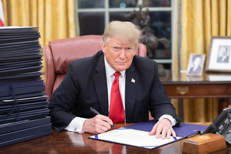 President Trump signing paperwork from his desk in the Oval Office.