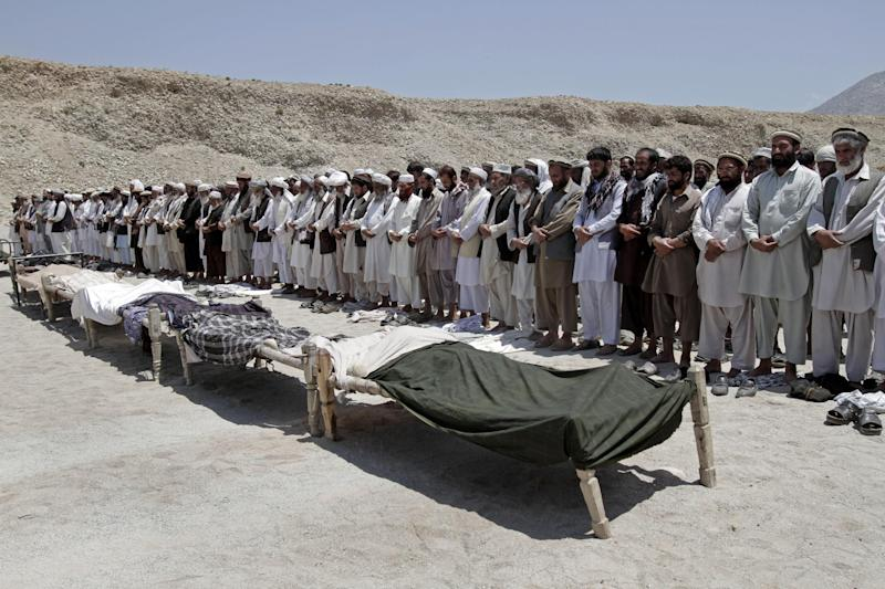Afghan men offer funeral prayers near the bodies of 7 civilians killed, by a roadside bomb in the Alingar district of Laghman province, east of Kabul, Afghanistan, Monday, June 03, 2013. A statement from the provincial government said a group of four women and two children had gone with a male driver into the hills to collect firewood. On their way back, their vehicle hit the mine and all inside were killed. (AP Photo/Rahmat Gul)
