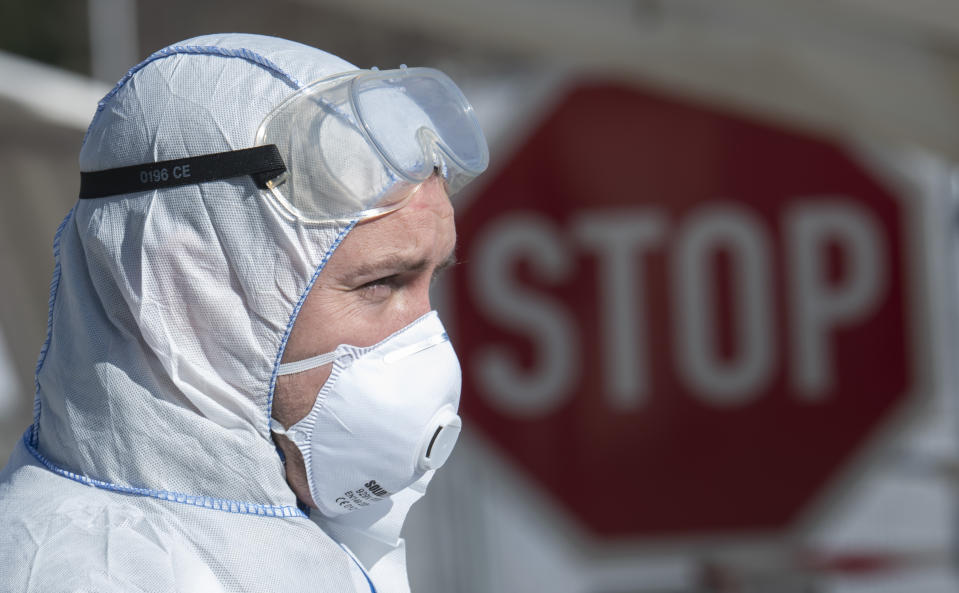 Corporal Mathias Jahn, left, member of the German armed forces Bundeswehr, stands in front of a mobile coronavirus test station and demonstrates his work in a test run after a press conference at a drive-through (drive-in) COVID-19 testing center in Gera, Germany, Wednesday, April 1, 2020. The appointment-only drive-through testing center began twelfe days ago. Medical staff reach into a car to take a nasopharyngeal swab from a patient. For most people, the new coronavirus causes only mild or moderate symptoms, such as fever and cough. For some, especially older adults and people with existing health problems, it can cause more severe illness, including pneumonia. (AP Photo/Jens Meyer)