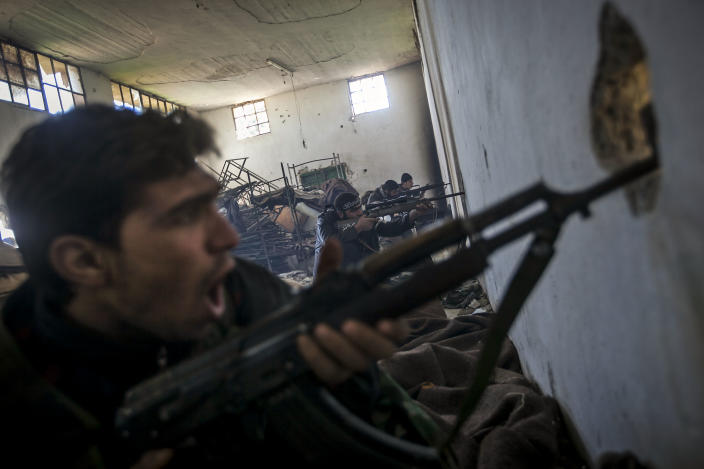 In this Saturday, Dec. 15, 2012 photo, Free Syrian Army fighters aim their weapons as they chant religious slogans during heavy clashes with government forces at a military academy besieged by the rebels north of Aleppo, Syria. Free Syrian Army fighters took control over the military academy after battling government forces for several hours. (AP Photo/Narciso Contreras)