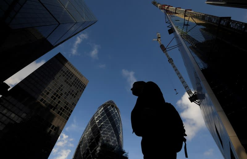 A worker walks past office skyscrapers in the City of London financial district, London, Britain
