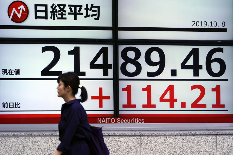 A woman walks past an electronic stock board showing Japan's Nikkei 225 index at a securities firm in Tokyo Tuesday, Oct. 8, 2019. (AP Photo/Eugene Hoshiko)