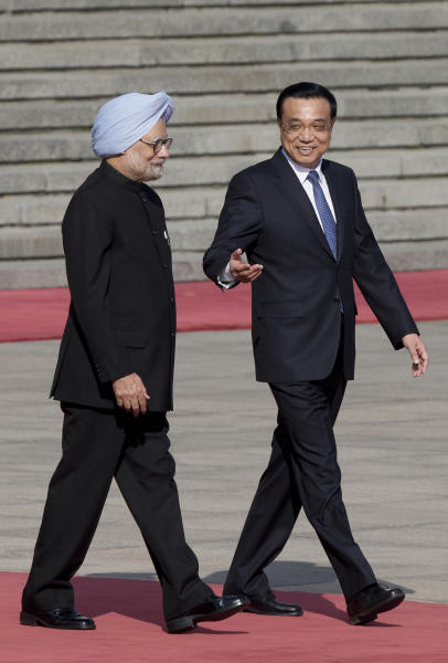 Indian Prime Minister Manmohan Singh, left, chats with Chinese Premier Li Keqiang during a welcome ceremony outside the Great Hall of the People in Beijing Wednesday, Oct. 23, 2013. China and India signed a confidence-building accord Wednesday to cooperate on border defense following a standoff between armed forces of the two Asian giants in disputed Himalayan territory earlier this year. (AP Photo/Andy Wong)
