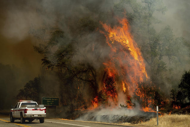 <p>Flames from the Carr Fire lick above a Cal Fire truck in Whiskeytown, Calif., on July 27, 2018. (Photo: Noah Berger/AP) </p>
