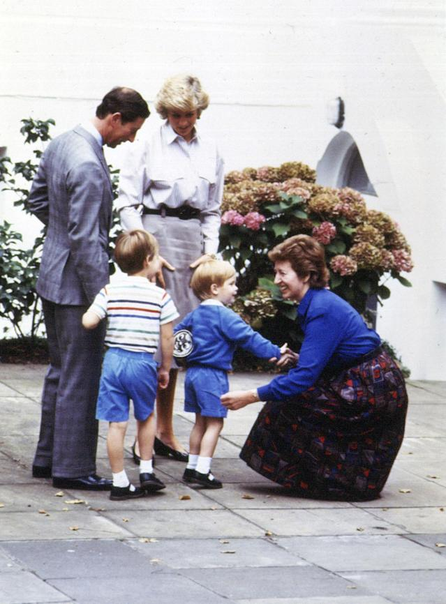 A three-year-old Prince Harry holds a Thomas the Tank Engine bag as he shakes the hand of headmistress Jane Mynors as he arrives for his first day of nursery school in 1987. (PA Images)