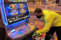 An employee cleans a slot machine at the Hard Rock casino in Atlantic City, N.J., on July 2, 2020, the day it reopened after being closed for just over three months due to the coronavirus outbreak. New Jersey's casinos and horse tracks won $2.88 billion in 2020, a decrease of nearly 17% from 2019, according to figures released Wednesday, Jan. 13, 2021, by the New Jersey Division of Gaming Enforcement. (AP Photo/Wayne Parry)