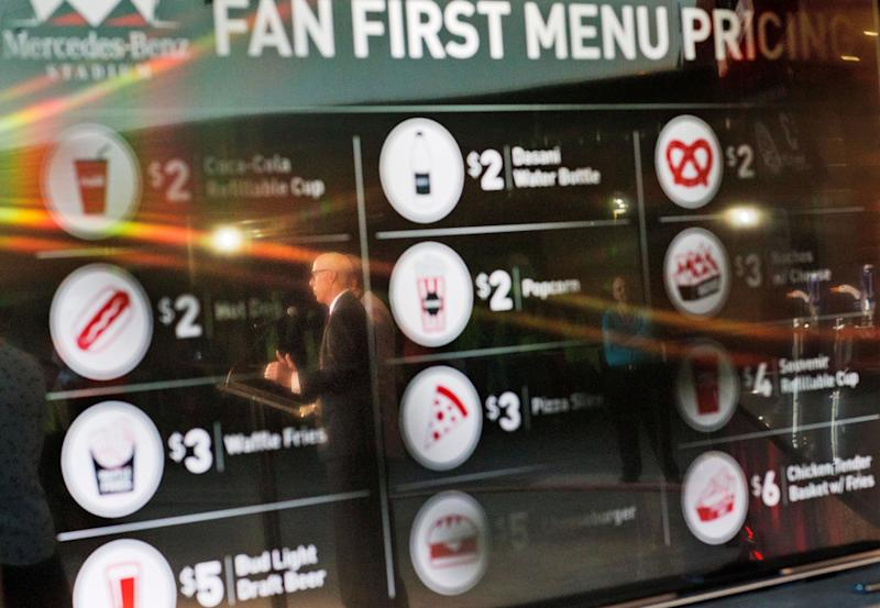 Atlanta Falcons president and CEO Rich McKay is reflected in a screen displaying the proposed concession stand menu prices inside the Falcons new stadium currently under construction Monday, May 16, 2016, in Atlanta. Falcons owner Arthur Blank says the Mercedes-Benz Stadium is on schedule to open in June, 2017 as scheduled and he's hoping it will be announced next week as the site of a Super Bowl. The Falcons also unveiled their new food and beverage plan which includes $2 hot dogs and soft drinks, a sharp decrease from current prices at the Georgia Dome. (AP Photo/David Goldman)