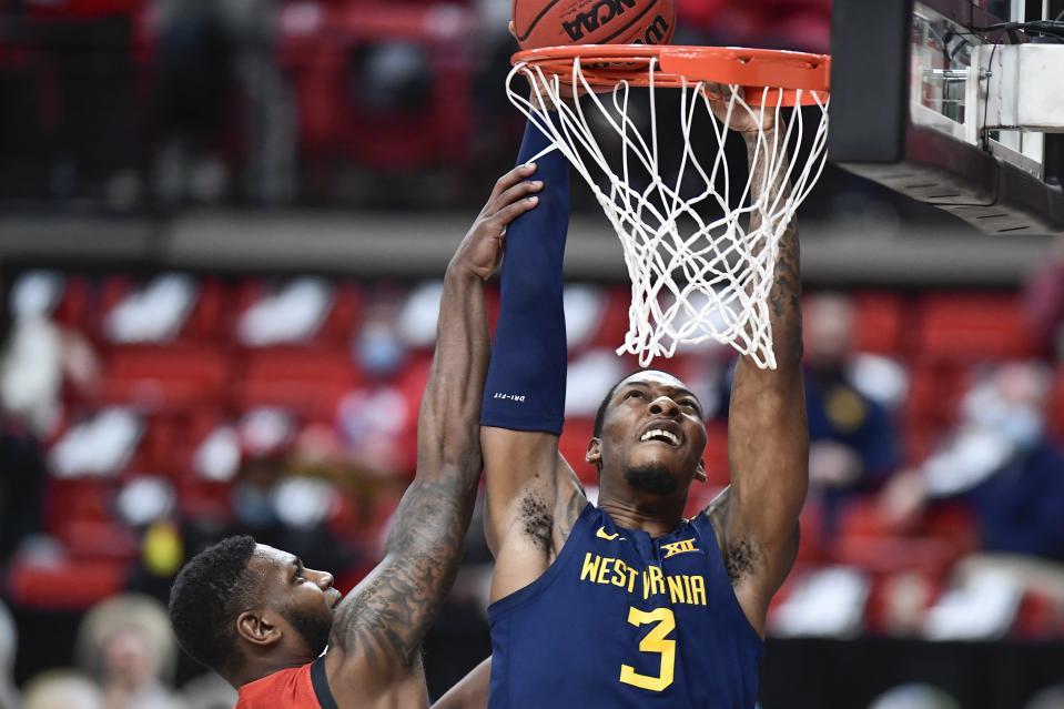 West Virginia's Gabe Osabuohien (3) attempts to shoot over Texas Tech's Jamarius Burton (2) during the second half of an NCAA college basketball game in Lubbock, Texas, Tuesday, Feb. 9, 2021. (AP Photo/Justin Rex)