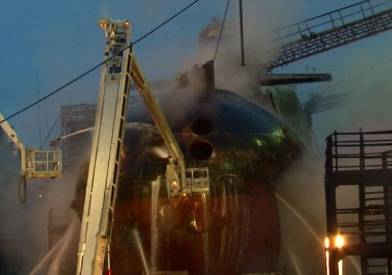In this video image from Ru-RTR Russian state channel, firefighters spray water on the Yekaterinburg nuclear submarine in a dock at the Roslyakovo shipyard in the Murmansk region, Russia, Friday, Dec. 30, 2011. A fire that erupted while the Yekaterinburg was in drydock for repairs at the town of Roslyakovo near Murmansk has left seven crewmembers injured after they inhaled poisonous fumes from the blaze. (AP Photo/Ru-RTR Russian state channel/ Via APTN)