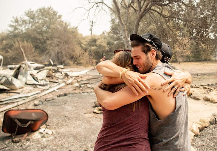 Austin Giannuzzi cries while embracing family members at the burned remains of their home during the LNU Lightning Complex Fire in Vacaville, Calif., on Aug. 23.