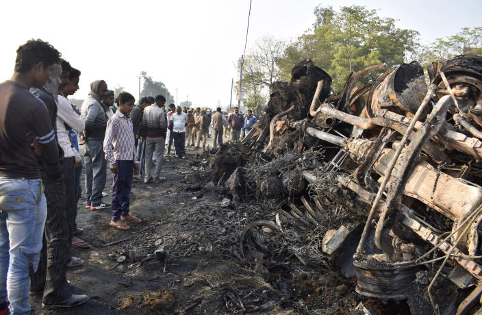 People look at what remains of a bus that caught fire after ramming into a truck in Kannauj, in the northern Indian state of Uttar Pradesh, Saturday, Jan. 11, 2020. At least 20 people died when in the accident, police said. Another 21 people were taken to a hospital, some of them in critical condition, following the crash late Friday, said senior police officer Mohit Aggarwal. (AP Photo)
