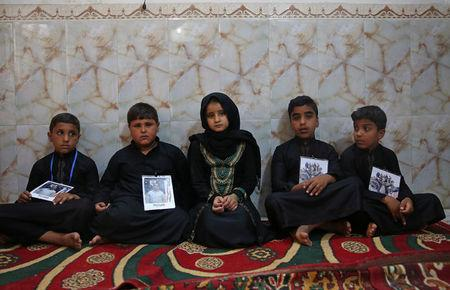 Children hold pictures of their fathers, who were killed by Islamic State militants at Kirkuk road, in Kerbala, Iraq July 5, 2018. Picture taken July 5, 2018. REUTERS/Abdullah Dhiaa al-Deen