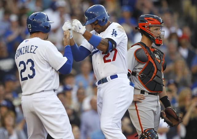 Los Angeles Dodgers' Adrian Gonzalez, left, congratulates Matt Kemp, center, after Kemps two-run home run, as San Francisco Giants catcher Buster Posey stands at the plate in the fourth inning of a baseball game Sunday, April 6, 2014, in Los Angeles. It was Kemp's second home run of the game. (AP Photo/Alex Gallardo)