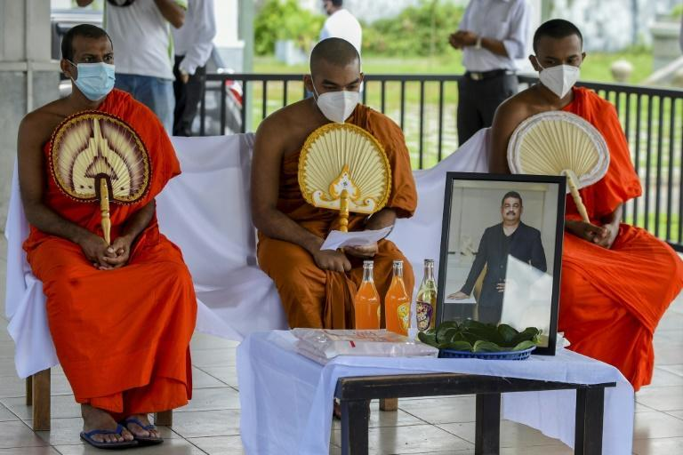 Buddhist monks perform the last rites during the funeral of Eliyantha White, a local shaman who claimed he had super natural powers to end the pandemic (AFP/ISHARA S. KODIKARA)