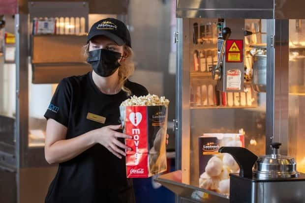Kaelyn Cherbonneau handles some popcorn for a customer at Landmark Cinema in Kingston, Ont., on Friday, July 16, 2021.  Ontario has moved into Step 3 of its COVID-19 reopening plan, with indoor dining and movie theatres once again possible. (Lars Hagberg/The Canadian Press - image credit)