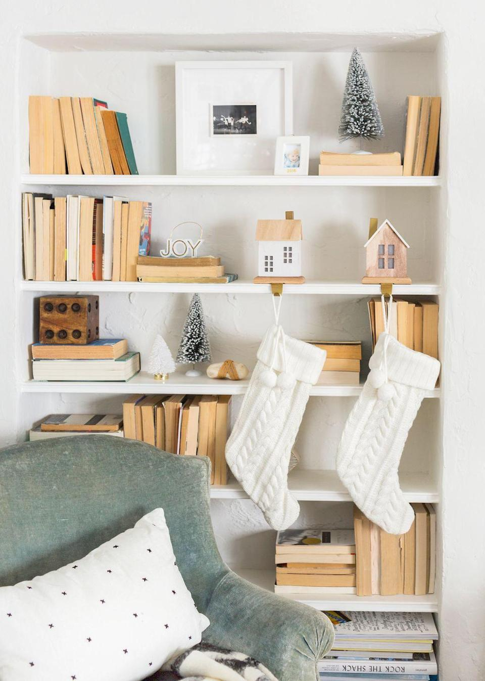 "<p>If you like the neutral colors in this reading nook designed and styled by <a href=""https://stylebyemilyhenderson.com/"" rel=""nofollow noopener"" target=""_blank"" data-ylk=""slk:Emily Henderson"" class=""link rapid-noclick-resp"">Emily Henderson</a> for the holidays, recreate it with a few cream knit stockings and miniatures. Instead of buying them, get crafty with mini wood house kit. Use <a href=""https://www.hgtv.com/lifestyle/holidays/modern-wood-christmas-house"" rel=""nofollow noopener"" target=""_blank"" data-ylk=""slk:this tutorial"" class=""link rapid-noclick-resp"">this tutorial</a> for guidance. </p>"