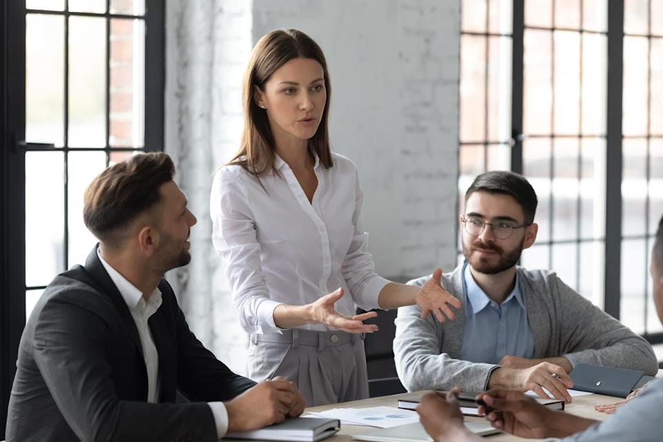 Attractive young mentor businesswoman conducts coaching in boardroom at company meeting. Confidence woman training corporate team at briefing. Young employee share thoughts standing at table.
