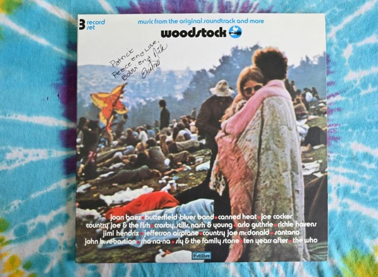 "A copy of the live album of ""Woodstock: Music from the Original Soundtrack and More"" signed by couple Bobbi and Nick Ercoline, who are featured in the album cover's image"