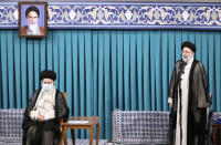In this photo released by an official website of the office of the Iranian supreme leader, newly elected President Ebrahim Raisi, right, speaks after receiving official seal of approval of Supreme Leader Ayatollah Ali Khamenei, left, in an endorsement ceremony in Tehran, Iran, Tuesday, Aug. 3, 2021. A portrait of the late revolutionary founder Ayatollah Khomeini hangs at top left. (Office of the Iranian Supreme Leader via AP)